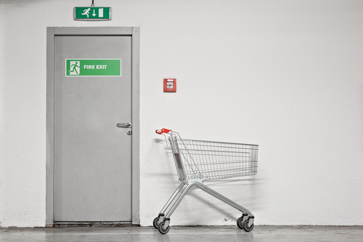 Photo of shopping cart next to fire exit door.