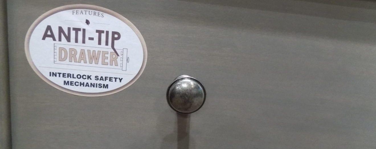 Image shows a safety sticker on a dresser drawer