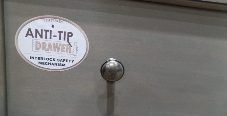 Image shows a safety sticker on a dresser drawer