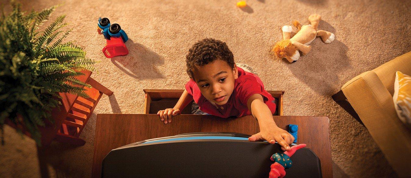 Photo shows a boy climbing up a dresser